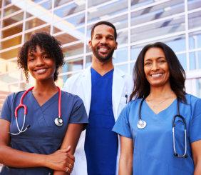 3 nurses outside the hospital facing the camera