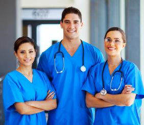 3 smiling nurses facing the camera inside the hospital